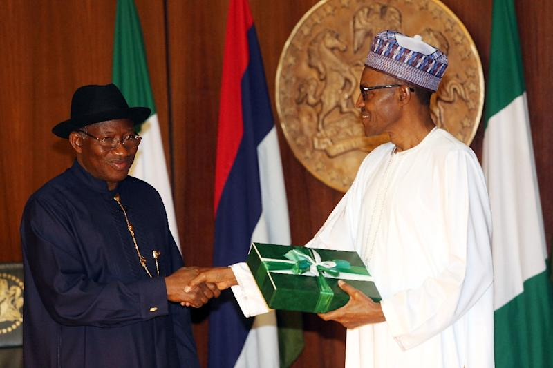 President-elect Mohammadu Buhari (R) shakes hands with then president Goodluck Jonathan as he receives handover notes from him in Abuja on May 28, 2015 (AFP Photo/)