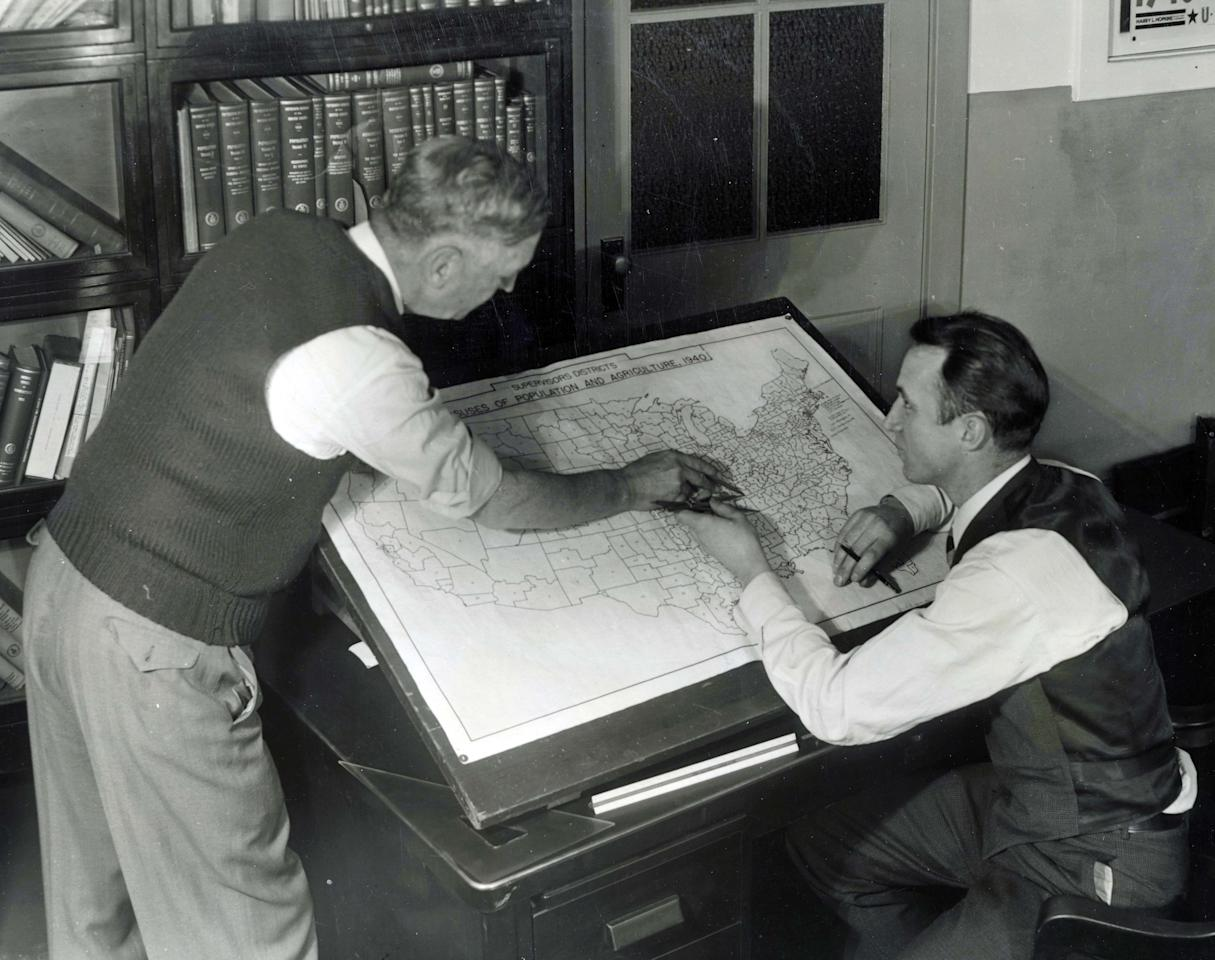 In this undated photo provided by the Franklin D. Roosevelt Presidential Library and Museum, staffers at the U.S. Census Bureau in Washington mark up a map for use in the 1940 census. The map shows approximately 147,000 enumeration districts for census-taking purposes and will ensure against overlapping activities of census takers, or enumerators, and also to avoid missing any territory. (AP Photo/Franklin D. Roosevelt Presidential Library)