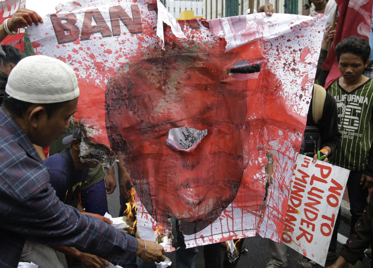 <p>Protesters burn a picture of President Donald Trump during a rally near the U.S. Embassy to protest this weekend's visit of Trump on Saturday, Nov. 11, 2017 in Manila, Philippines. (Photo: Aaron Favila/AP) </p>