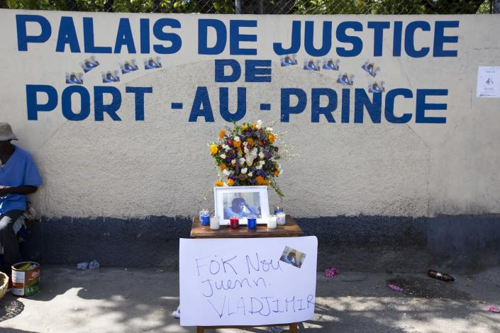 "Flowers, candles and a sign with a message that reads in Creole: ""We must find Vladjimir,"" adorn a makeshift memorial dedicated to missing photojournalist Vladjimir Legagneur, during a sit-in outside a courthouse organized by the Association of Journalists, in Port-au-Prince, Haiti, Monday, June 4, 2018. Legagneur disappeared on March 14 after entering the community of Grand Ravine, considered one of the poorest and most dangerous in Port-au-Prince. He has not been heard of since, and none of his belongings have been found as anger and frustration grows over a lack of answers from police and justice officials. (AP Photo/Dieu Nalio Chery)"