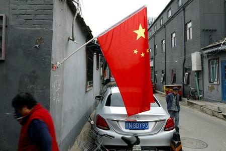 People walk at a hutong alley decorated with Chinese national flags during the ongoing 19th National Congress of the Communist Party of China, in Beijing, China October 21, 2017. REUTERS/Tyrone Siu/Files