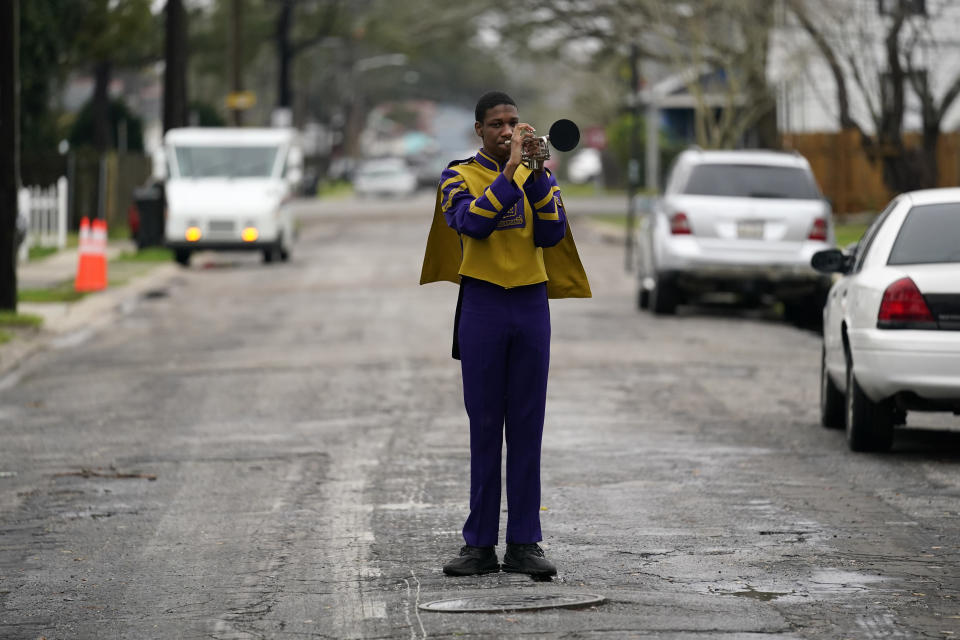 Elvin King III a senior at Warren Easton High and member of their marching band, which will not march because parades are cancelled, poses for a portrait in front of his home in New Orleans, Friday, Feb. 12, 2021. New Orleans' annual pre-Lenten Mardi Gras celebration is muted this year because of the coronavirus pandemic. Parades canceled. Bars closed. Crowds suppressed. Mardi Gras joy is muted this year in New Orleans as authorities seek to stifle the coronavirus's spread. And it's a blow to the tradition-bound city's party-loving soul. (AP Photo/Gerald Herbert)