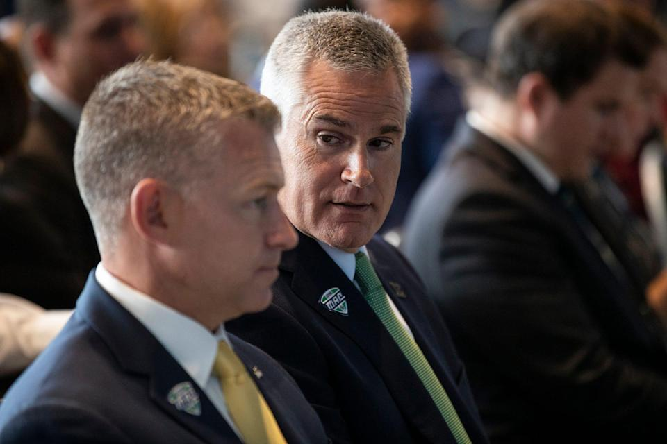 Easter Michigan head football coach Chris Creighton, right, talks to Eastern Michigan athletic director Scott Wetherbee during the MAC football media day at Ford Field on Tuesday, July 20, 2021.
