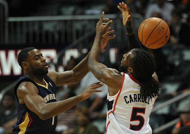 New Orleans Pelicans' Tyreke Evans, left, attempts to steal from Atlanta Hawks' DeMarre Carroll (5) in the first half of an NBA basketball game Friday, March 21, 2014, in Atlanta. (AP Photo/David Tulis)