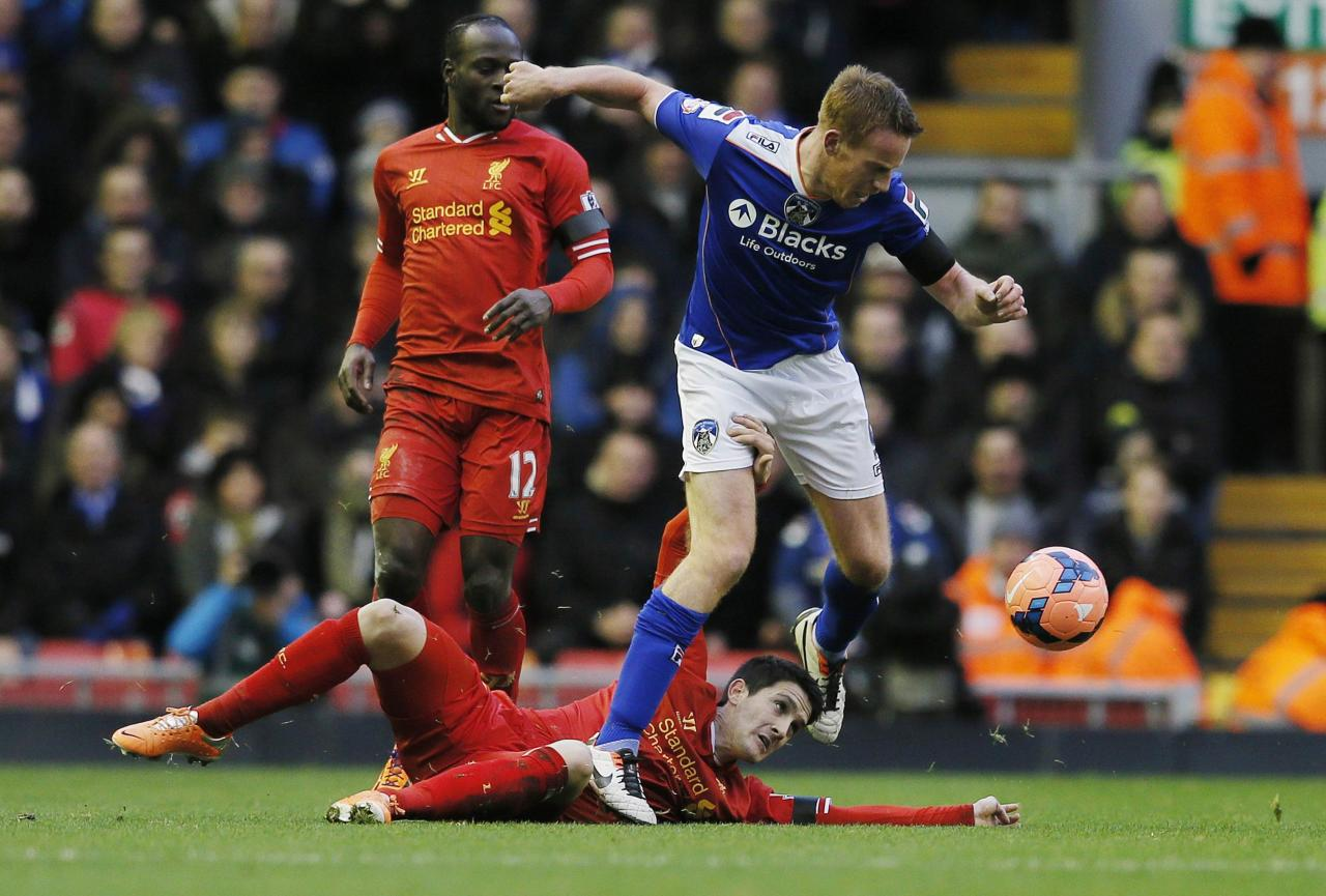Oldham Athletic's Adam Rooney challenges Liverpool's Luis Alberto during their FA Cup third round soccer match at Anfield in Liverpool January 5, 2014. REUTERS/Phil Noble (BRITAIN - Tags: SPORT SOCCER)