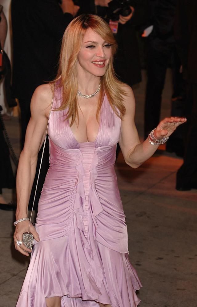 <p>Madonna has remained a style chameleon for decades, and she gave us major disco vibes in this 2006 Versace number. The feathered hair makes the look. (Photo: PA) </p>