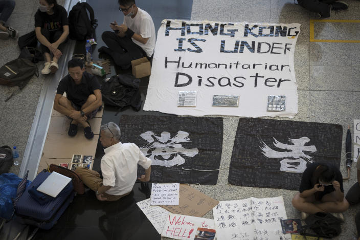 A traveler, bottom left, sits with protesters during a sit-in rally at the Hong Kong International Airport in Hong Kong, Tuesday, Aug. 13, 2019. (Photo: Vincent Thian/AP)