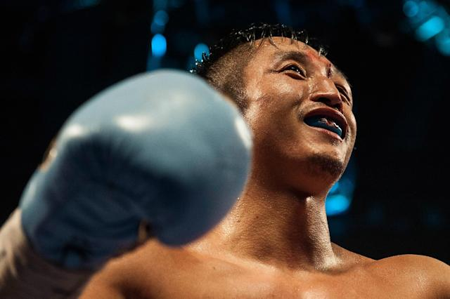 Zou Shiming of China smiles during his flyweight boxing bout against Kwanpichit Onesongchaigym of Thailand in Macau on November 23, 2014 (AFP Photo/Xaume Olleros)
