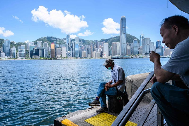 A man wearing a face mask sits along the Kowloon side of Victoria Harbour which faces the skyline of Hong Kong Island, in Hong Kong on July 13, 2020. (Photo by Anthony WALLACE / AFP) (Photo by ANTHONY WALLACE/AFP via Getty Images)