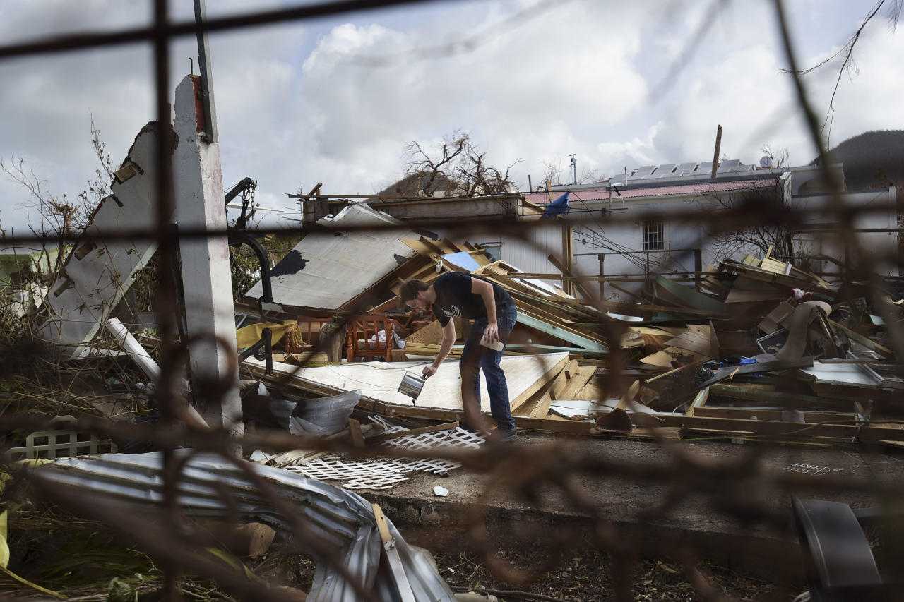 <p>Lex Kools leaves food and water for his neighbors' dogs in the Cole Bay community, in the aftermath of Hurricane Irma, in St. Martin, Tuesday, Sept. 12, 2017. Hundreds of people across an island shared by Dutch St. Martin and French St. Martin are trying to rebuild the lives they had before it was pummeled by a Category 5 storm. (Photo: Carlos Giusti/AP) </p>