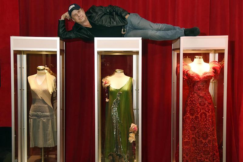 Todd Fisher poses atop glass cases displaying three dresses that Reynolds wore during her career: Chris Pizzello/Invision/AP