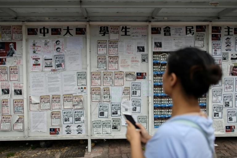 "A student walks past posters calling for and against semi-autonomous Hong Kong to split from the mainland, on the ""democracy wall"" of the Chinese University of Hong Kong"
