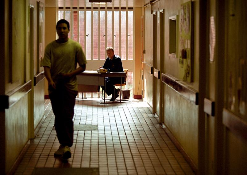 A prisoner walks down a corridor watched by an officer at Feltham Young Offenders Institution in London. The prison was savaged as an affront to civilisation and rotten to the core in the most blistering report yet by the Chief Inspector of Prisons. Sir David Ramsbotham said Feltham was guilty of institutionalised neglect with youngsters spending up to 22 hours a day in filthy, cold cells with nothing to do in a numbing routine. (Photo by Matthew Fearn - PA Images/PA Images via Getty Images)