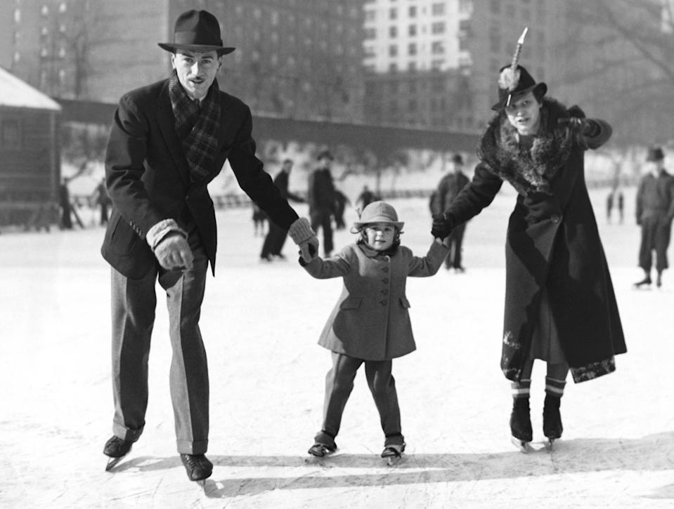 "A young family enjoys the first day of skating on The Pond near 59th Street and Fifth Avenue in <a href=""https://www.cntraveler.com/activities/new-york/central-park?mbid=synd_yahoo_rss"" rel=""nofollow noopener"" target=""_blank"" data-ylk=""slk:Central Park"" class=""link rapid-noclick-resp"">Central Park</a>. Though The Pond would eventually close to skaters, the park now has two ice skating rinks—Wollman Rink and Lasker Rink—with skate and locker rentals available."