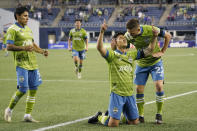 Seattle Sounders forward Fredy Montero kneels on the pitch as he celebrates with Kelyn Rowe right, and Raul Ruidiaz after scoring a goal against Minnesota United during the second half of an MLS soccer match Friday, April 16, 2021, in Seattle. The Sounders won 4-0. (AP Photo/Ted S. Warren)