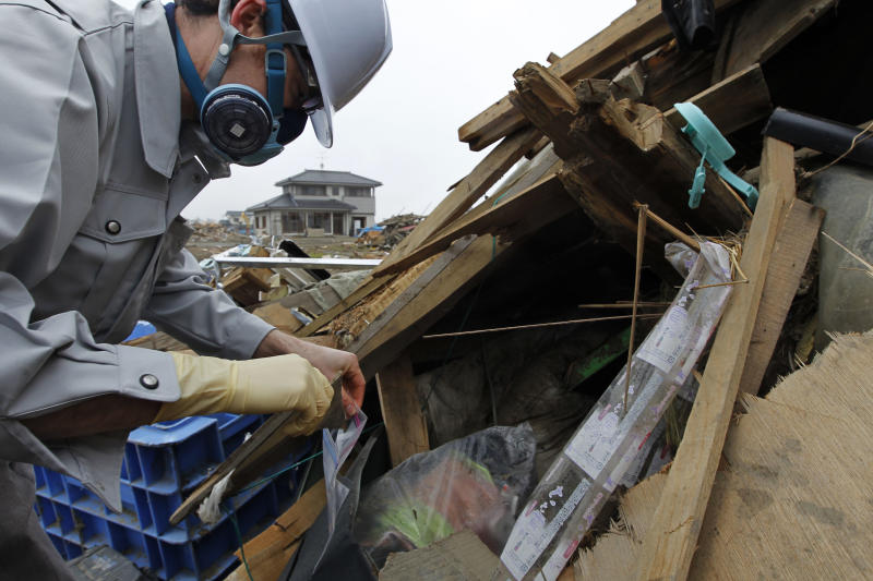 In this photo taken on April 22, 2011, EFA Laboratory manager Eric Eguina puts a piece of a material into a plastic bag while looking for materials possibly containing asbestos in an area devastated by the March 11 tsunami in Natori, Miyagi Prefecture, northeastern Japan. Inside the chunks of slate and wallboard smashed and scattered by Japan's tsunami hides a health risk that has been overshadowed by contamination from a leaking nuclear plant: the odorless and nearly invisible threat of asbestos. (AP Photo/Hiro Komae)