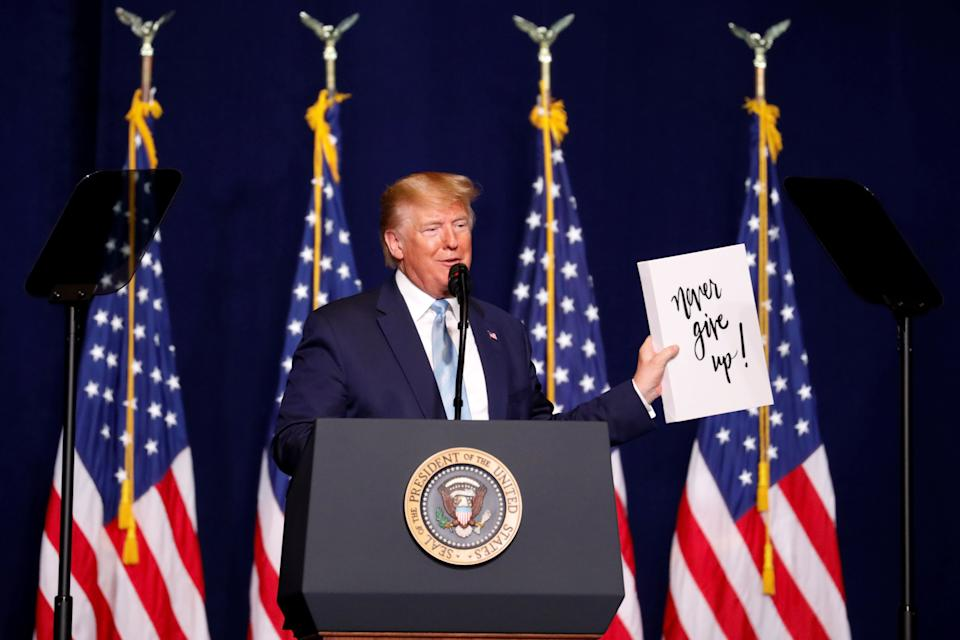 "Trump holds a sign that reads, ""Never give up!"" as he speaks to evangelical supporters in Miami on Jan. 3, 2020. (Photo: Eva Marie Uzcategui/Reuters)"