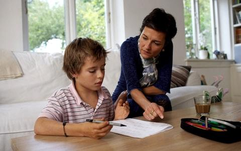 Woman assisting son (10-12) with homework - Credit: photonica