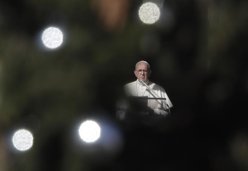 Framed by a Christmas tree, Pope Francis delivers his speech during the Angelus noon prayer he delivered from his studio window overlooking St. Peter's Square at the Vatican, Saturday, Dec. 8, 2018. (AP Photo/Alessandra Tarantino)