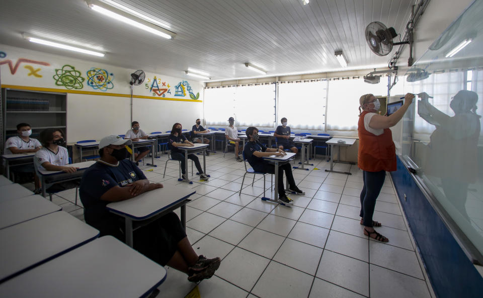 SAO PAULO, BRAZIL - OCTOBER 23: Students attend a face-to-face class maintaining social distance at the Teacher Milton da Silva Rodrigues state schoolas part of the gradual return of in-person education amidst the coronavirus (COVID-19) pandemic on October 23, 2020 in Sao Paulo, Brazil. Public and private schools in the state can reopen the doors to carry out on-site extracurricular activities to reinforce and welcome students. (Photo by Miguel Schincariol/Getty Images)