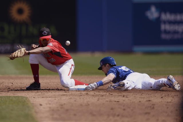 Toronto Blue Jays Cavan Biggio, right, slides into second as the throw gets away from Canada Junior National Team short stop Cesar Valero, left, during the second inning of a spring training baseball game Saturday, March 17, 2018, in Dunedin, Fla. Biggio would advance to third on the throwing error. (AP Photo/Jason Behnken)