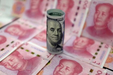 Benjamin Franklin U.S. 100-dollar banknote and Chinese 100-yuan banknotes depicting the late Chinese Chairman Mao Zedong, are seen in a picture illustration in Beijing, China, January 21, 2016. REUTERS/Jason Lee/File Photo