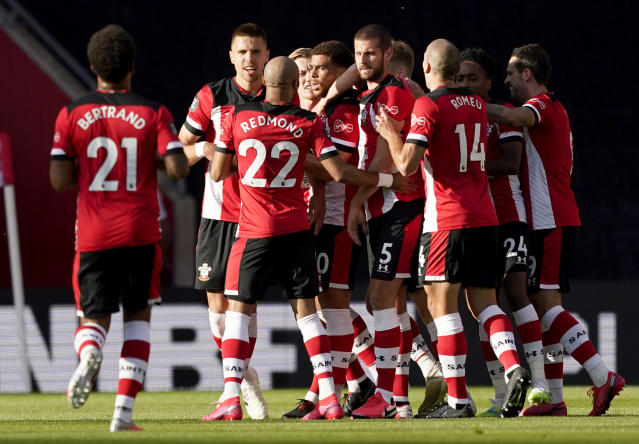 Southampton's Che Adams, centre, is congratulated by teammates after scoring his team's first goal during the English Premier League soccer match between Southampton and Manchester City at St. Mary's Stadium in Southampton, England, Sunday, July 5, 2020. (AP Photo/Will Oliver,Pool)