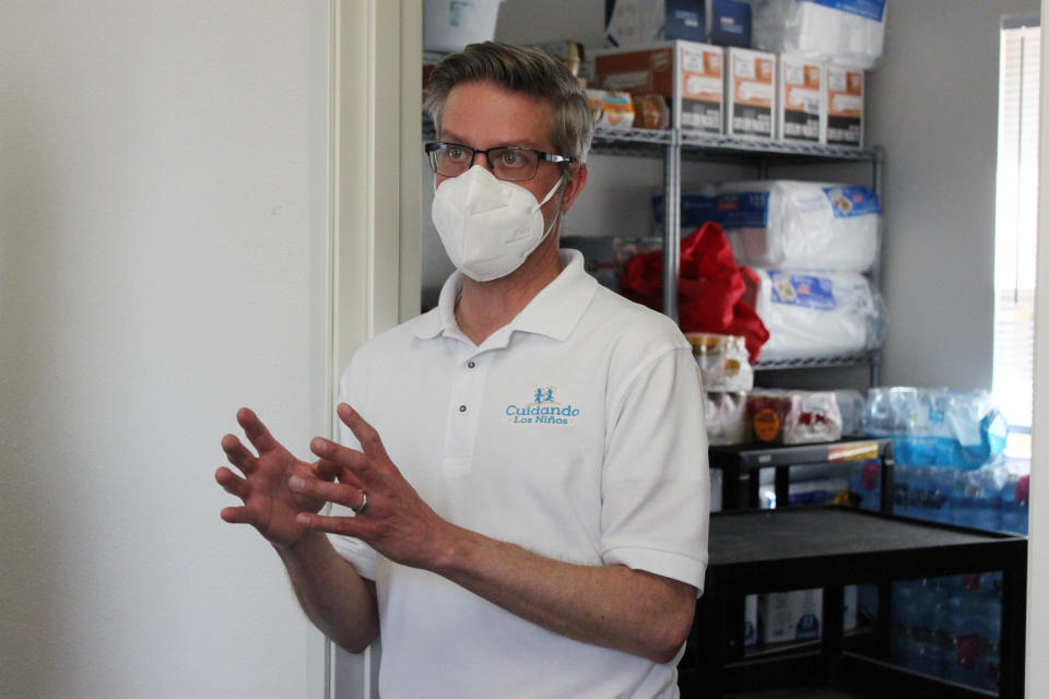 This May 4, 2021 image shows executive director Jeffrey Hoehn talking about some of the needs that single mothers have when trying to transition from homelessness, while standing in front of one of the supply rooms at Cuidando Los Ninos in Albuquerque, N.M. The charity provides housing, child care and financial counseling for mothers, all of whom will benefit from expanded Child Tax Credit payments that will start flowing in July to roughly 39 million households. (AP Photo/Susan Montoya Bryan)