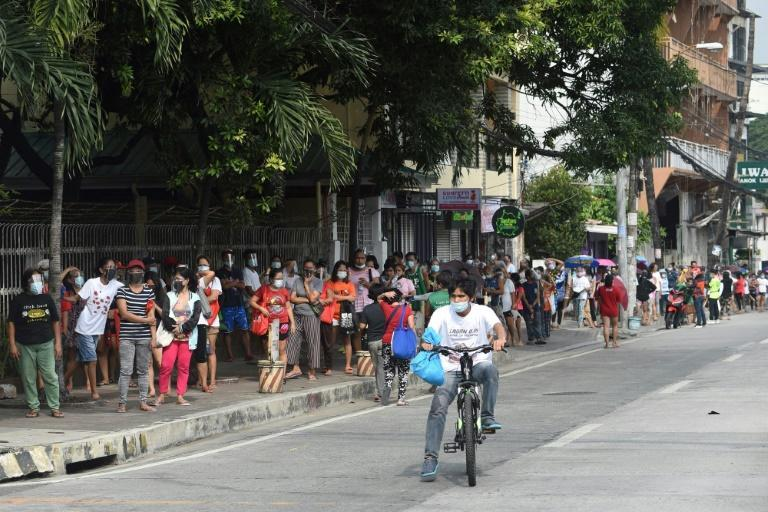 Residents queue to collect free food packets from a food bank run by volunteers in Quezon City