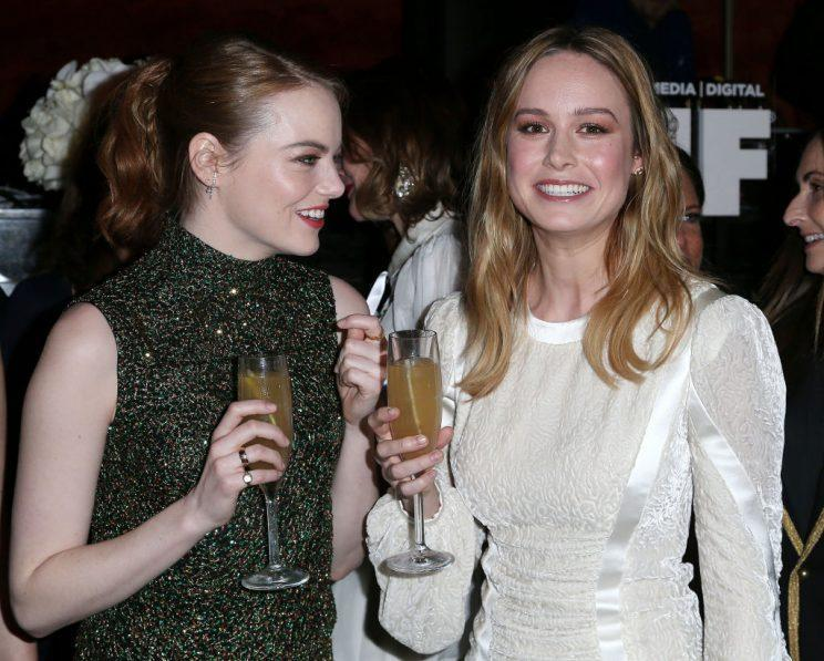 Emma Stone and Brie Larson, in McQueen, get bubbly. (Photo: Getty Images)