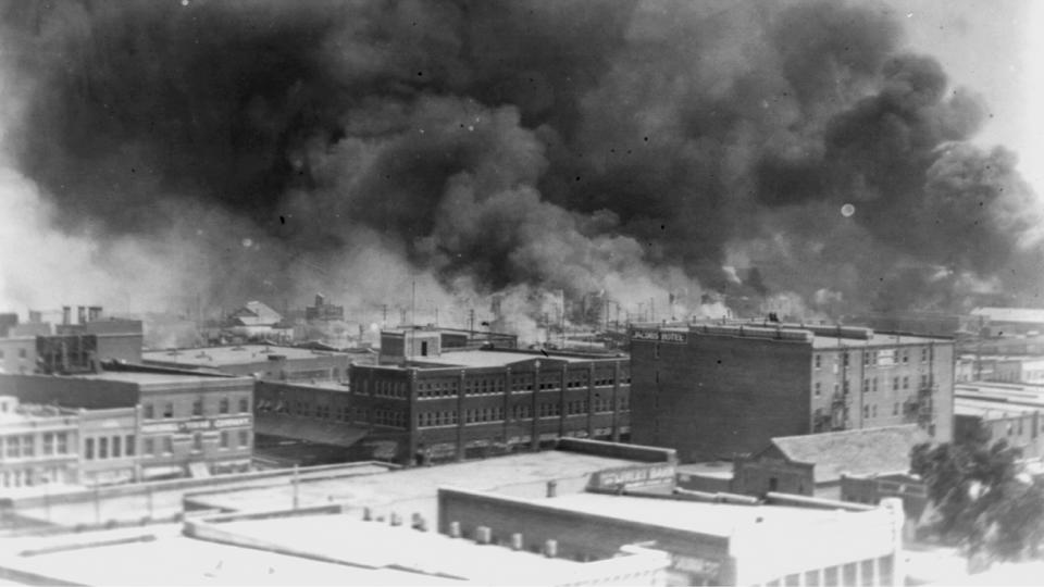 In this 1921 image provided by the Library of Congress, smoke billows over Tulsa, Okla. For decades, when it was discussed at all, the killing of hundreds of people in a prosperous black business district in 1921 was referred to as the Tulsa race riot. (Alvin C. Krupnick Co./Library of Congress via AP)
