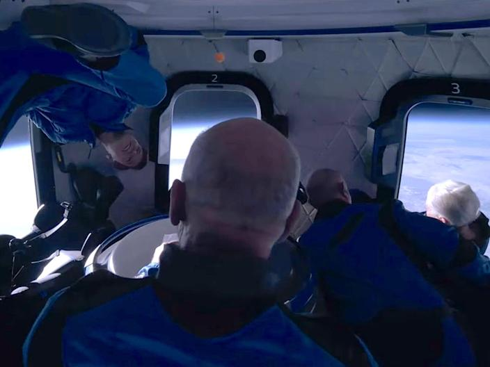 jeff bezos and three other passengers in jumpsuits float around spaceship cabin earth in background