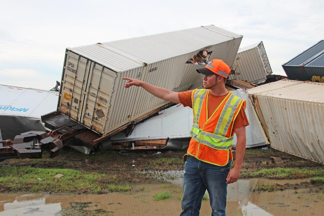 Tyler Shrum, a worker for the highway department, points to other train cars that were derailed due to high winds in Otwell, Ark. on Thursday, June 5, 2014. Strong winds and flooding led to the deaths of at least three people in the South on Thursday as powerful thunderstorms moved through the region. (AP Photo/The Sun, Staci Vandagriff)