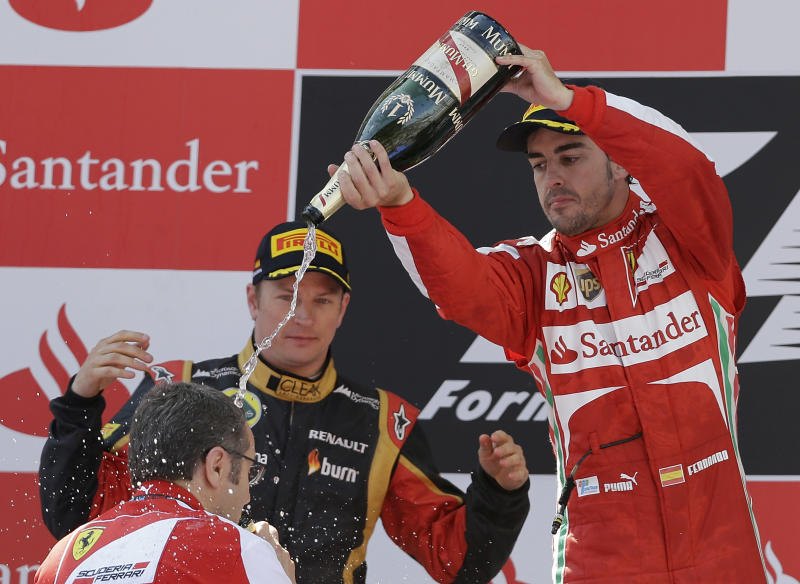 Ferrari driver Fernando Alonso of Spain pours Champagne on Ferrari team principal Stefano Domenicali, as second place Lotus driver Kimi Raikkonen of Finland watches on the podium after winning the Formula One Spanish Grand Prix, at the Catalunya racetrack in Montmelo, near Barcelona, Spain, Sunday, May 12, 2013. (AP Photo/Luca Bruno)