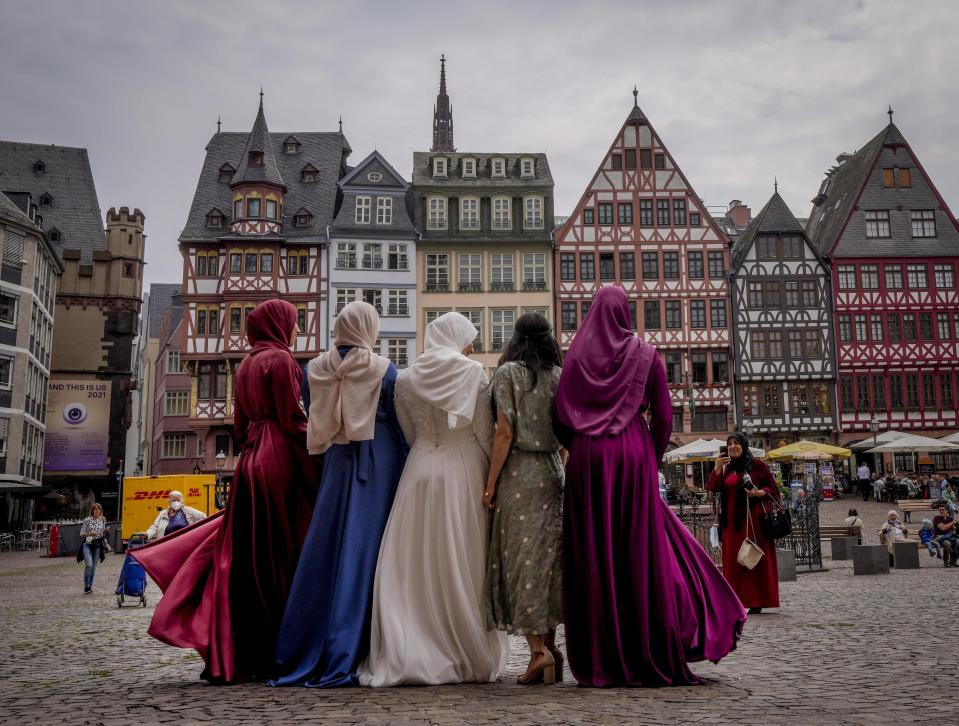A bride, center, and her friends pose for pictures after a wedding in the town hall at Roemerberg square in Frankfurt, Germany, Friday, June 25, 2021. (AP Photo/Michael Probst)