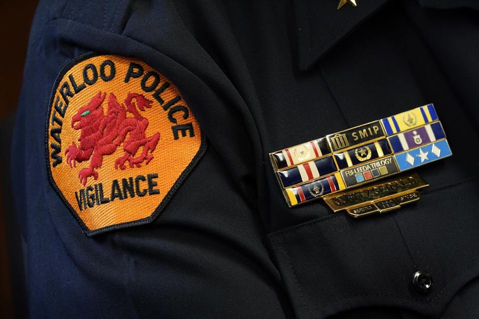 The Waterloo Police Dept. patch is seen on the arm of Chief Joel Fitzgerald as he speaks during an interview with The Associated Press, Tuesday, Sept. 7, 2021, in Waterloo, Iowa. Fitzgerald, the first Black police chief in Waterloo, is facing intense opposition from some current and former officers as he works with city leaders to reform the department, including the removal of its longtime insignia that resembles a Ku Klux Klan dragon. (AP Photo/Charlie Neibergall)