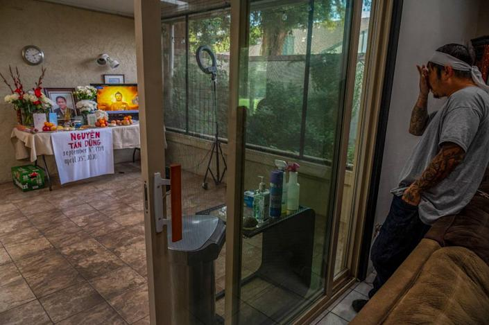 """Bao Nguyen, 45, says """"I think the whole community would be here,"""" as he waits for visitors to pay respects in his home, on Monday, May 4, 2020, where he and his wife Trang Nguyen created a prayer room to honor his father Dung Tan Nguyen who died on April 25. If it wasn't for the coronavirus, at least 15 Buddhist monks would've chanted prayers for him, but instead a video of chanting is played. Also in the room is an array of hand sanitizer, gloves, masks and cleaning fluids for those to use during their visit. """"It's kind of a sad way to do it. I'm not used to it. It's kind of the new way, new normal of our world right now,"""" said Nguyen who was explaining that only four people will be allowed at the funeral service and that only two people at a time will be allowed to lay flowers on the casket after it is lowered into the grave at the cemetery."""