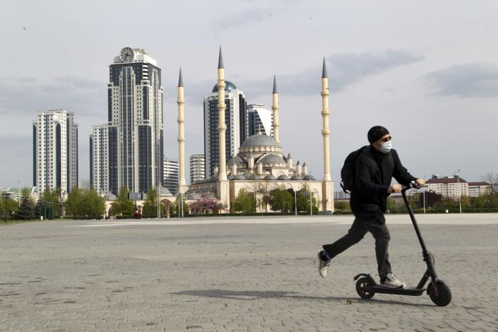"""A man rides a scooter through an empty square in front of closed the Central Mosque """"Heart of Chechnya"""" in Grozny, Russia, April 23, 2020. (AP Photo/Musa Sadulayev)"""