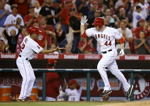 Los Angeles Angels' Mark Trumbo, right, is greeted by third base coach Dino Ebel as he rounds the bases after hitting a home run in the fourth inning of a baseball game against the Baltimore Orioles in Anaheim, Calif., Friday, July 6, 2012. (AP Photo/Jae C. Hong)
