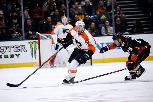 Philadelphia Flyers forward Kevin Hayes (13) keeps the puck away from Anaheim Ducks forward Ondrej Kase (25) during the first period of an NHL hockey game Sunday, Dec. 29, 2019, in Anaheim, Calif. (AP Photo/Ringo H.W. Chiu)