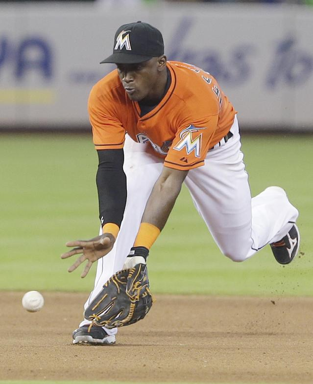 Miami Marlins shortstop Adeiny Hechavarria fields a ball hit by Los Angeles Dodgers' Carl Crawford during the fourth inning of a baseball game on Sunday, May 4, 2014, in Miami. Crawford was out at first. (AP Photo/Wilfredo Lee)