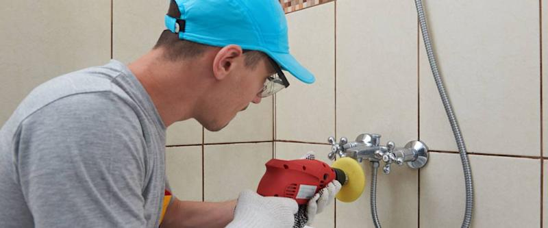 Man polishing bathroom faucet.