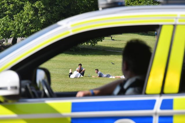 Police officers look at people relaxing in the sunshine on Primrose Hill in London (Picture: Getty)