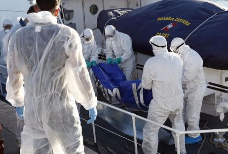 Health workers carry the dead body of a migrant, off a navy ship at the Sicilian harbour of Empedocle December 5, 2014. REUTERS/Antonio Parrinello