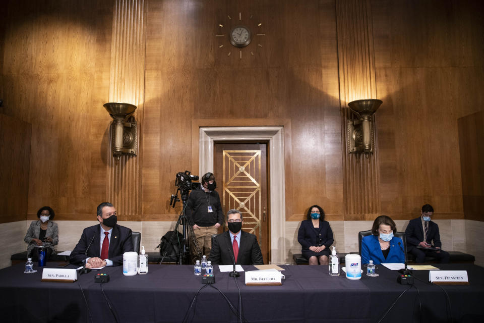 Xavier Becerra, center, listens during a confirmation hearing to be Secretary of Health and Human Services before the Senate Health, Education, Labor and Pensions Committee, Tuesday, Feb. 23, 2021 on Capitol Hill in Washington. Seated with Becerra are Sen. Alex Padilla, D-Calif., left, and Sen. Dianne Feinstein, D-Calif. (Sarah Silbiger/Pool via AP)