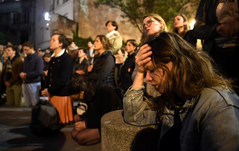 People kneel on the pavement as they pray outside watching flames engulf Notre-Dame Cathedral in Paris on April 15, 2019. (Photo: Eric Feferberg/AFP/Getty Images)