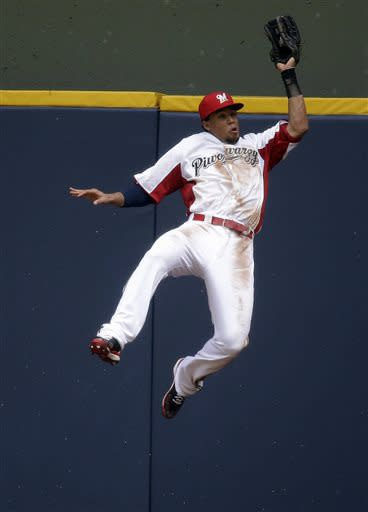 Milwaukee Brewers center fielder Carlos Gomez leaps to catch a ball hit by Atlanta Braves' Andrelton Simmons during the fourth inning of a baseball game on Sunday, June 23, 2013, in Milwaukee. Gomez was injured on the play and left the game. (AP Photo/Morry Gash)