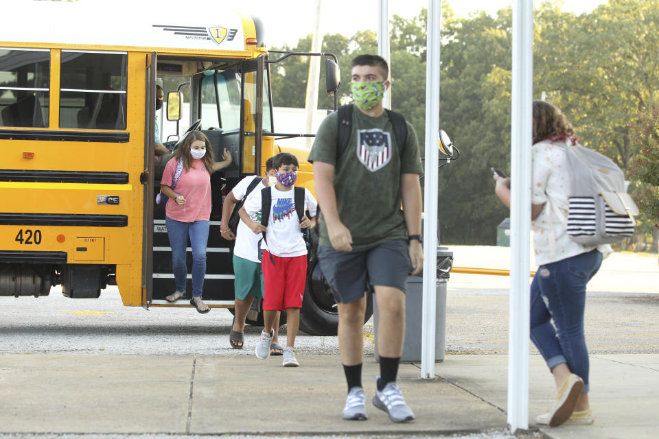 Students exit their school bus and head to their classrooms at Mooreville High School in Mooreville Miss., Thursday, August 6, 2020, as the school begins it's new school year.(Thomas Wells/Northeast Mississippi Daily Journal, Via AP)