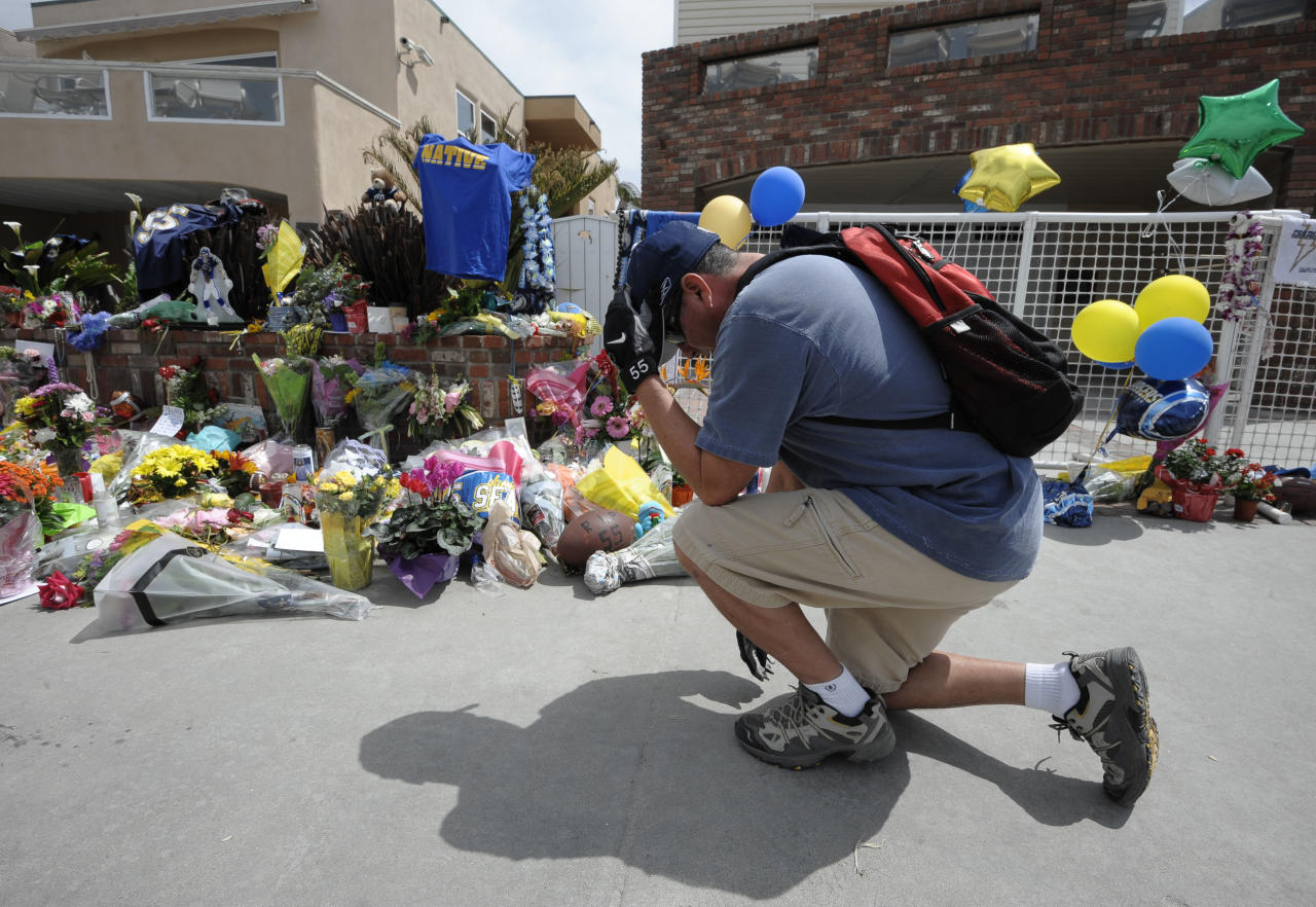 San Diego Chargers fan Dennis Telles bows down in front of a memorial in the driveway of the house of former NFL star Junior Seau Thursday, May 3, 2012, in Oceanside, Calif. Seau's death stunned the region he represented with almost reckless abandon. (AP Photo/Denis Poroy)