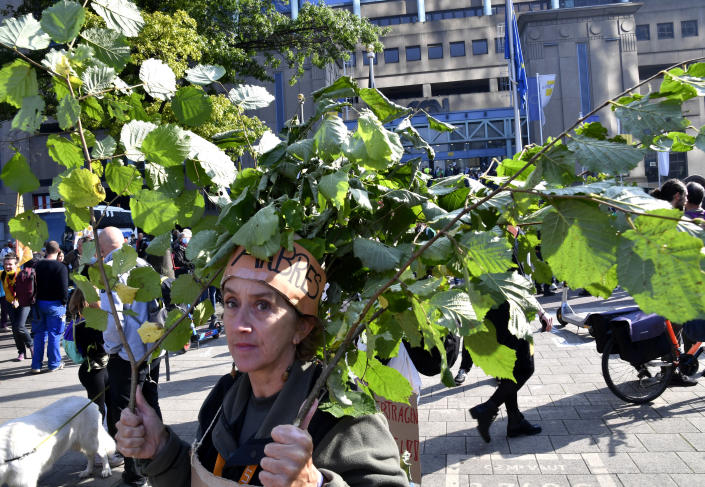A woman carries branches as she participates in a climate march in Brussels, Sunday, Oct. 10, 2021. Some 80 organizations are joining in a climate march through Brussels to demand change and push politicians to effective action in Glasgow later this month.(AP Photo/Geert Vanden Wijngaert)